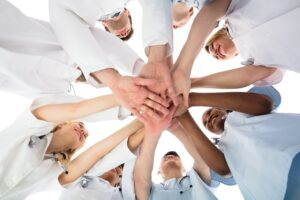 Low,Angle,View,Of,Smiling,Medical,Team,Stacking,Hands